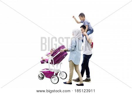 Image of young Muslim mother carrying baby in the stroller with her husband holding a boy isolated on white background