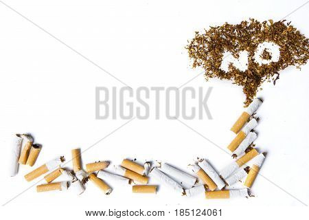 Close up No smoking sign made with broken cigarettes and tobacco isolated on white background