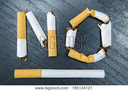 No smoking word written with broken cigarette on the table. Concept for quitting smoking