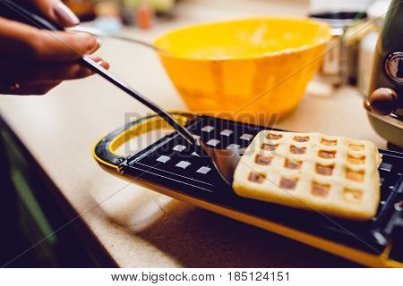 Waffle maker in the kitchen. Cook homemade waffles, Take out the prepared waffle