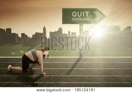 Obese female kneeling on the track with text of quit smoking on the sign board
