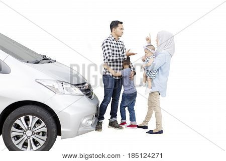 Muslim parents arguing in front of their children while standing with car isolated on white background