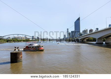 BRISBANE, AUSTRALIA - APRIL 29 2017: Brisbane CBD skyline and 1 William Street building with connecting Goodwill bridge and highway. Free City Hopper ferry commuting passengers on the Brisbane River
