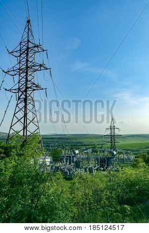 Electric substation in a forest with power lines
