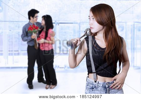 Teenage girl jealous and looking to romantic young couple while holding a beater tool