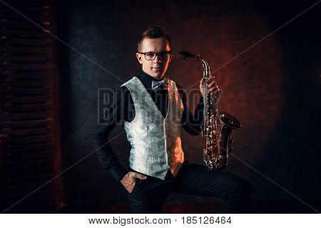 Male saxophonist posing with saxophone, jazz man