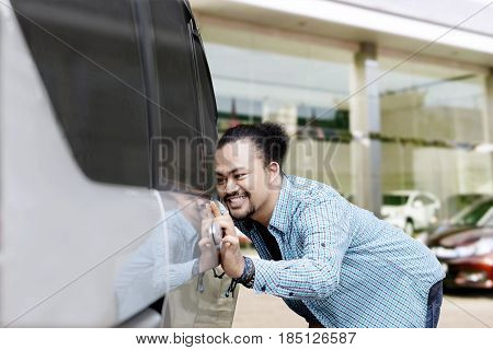 Portrait of a young Afro man smiling happy while touching a new car in the showroom