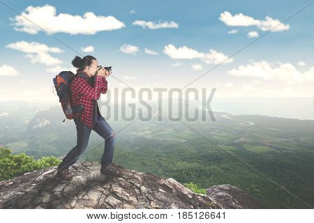 Image of young male standing on the mountain while taking a photo of amazing landscapes