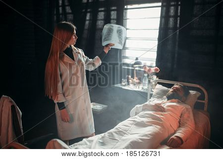Female doctor looking at x-ray picture of sick man