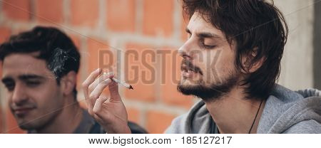 Closeup Of Friends Smoke Pot Or Hashish Joint In Ghetto