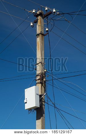Electric pillar with wires and internet box on dark blue sky