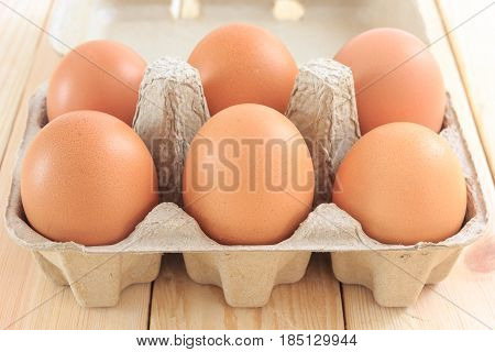 Egg in carton pack on wooden table Chicken Egg