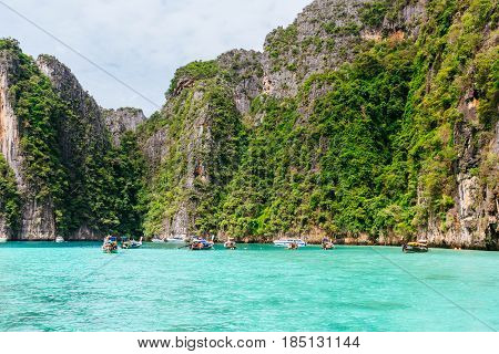 KOH PHI PHI, THAILAND - JULY 23: Motor boats on turquoise water of Pi Leh bay at snorkeling point famous tour lagoon in Phi Phi Islands on July 23 2016 in Koh Phi Phi island Thailand.