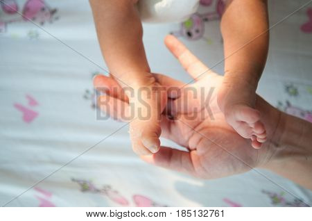 Close up foot of newborn girl with hands of her dad