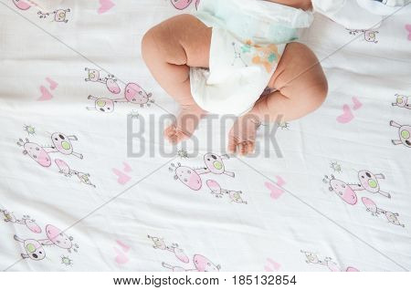 Close up foot of newborn girl with sun light. Focus on half part of newborn body.