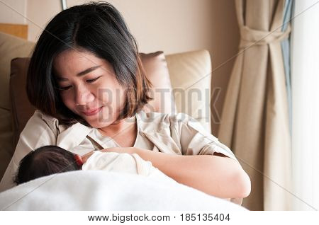 Mother breastfeeding her newborn baby beside window. Milk from mother's breast is a natural medicine to baby. Mother day bonding concept with newborn baby nursing.