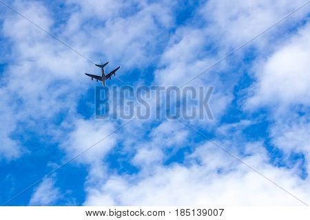 Airplane flies overhead into the vastness of the blue sky with white clouds.