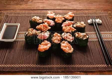 Appetizing japanese sushi. Set of tasty rolls served on brown straw mat, close up. Restaurant menu photo, traditional healthy seafood, food art.