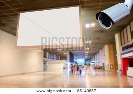 security CCTV camera with blank billboard with empty copy space in the airport for new advertisement with blurred interior airport background.