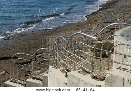 Shiny Metal Handrail Of Beach Stair On Splash Background.