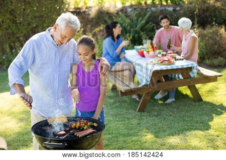 Grandfather and granddaughter preparing barbecue while family having meal in background