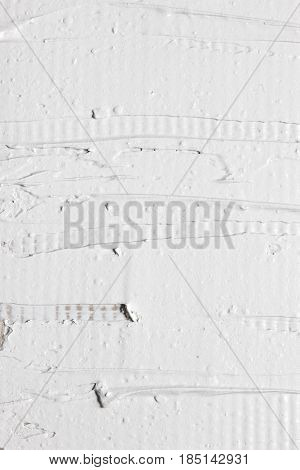 Rough surface, negligent texture of white plaster on the wall, closeup. Putty background, repair, building, interior material design concept