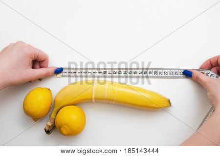 Penis size importance. Sex quality and woman satisfaction. Aroused big phallus with hard erection in condom with measure tape.