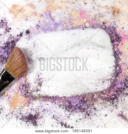 Makeup brush on white marble background, with traces of powder and blush forming a frame. A square template for a makeup artist's business card or flyer design, with copy space