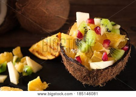 Juicy colorful fruits chopped in coconut shell on rustic wooden table, top view. Appetizing and tasty vegetarian dish, healthy food.