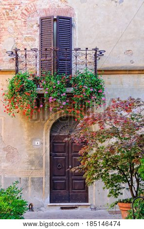 Half closed shutters during siesta on a balcony decorated by blooming flowers in Pienza, Tuscany, Italy