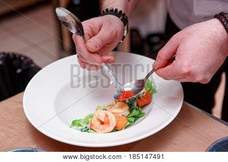 Chef is decorating prawn appetizer with salmon roe, commercial kitchen, slight motion blur, toned image