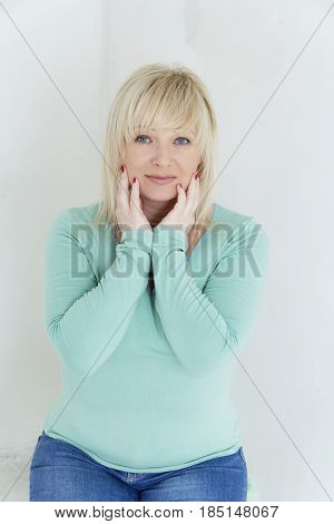 vertical portrait of blond woman with blue eyes in green