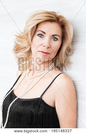 Vertical portrait blond woman with pearl beads on white background