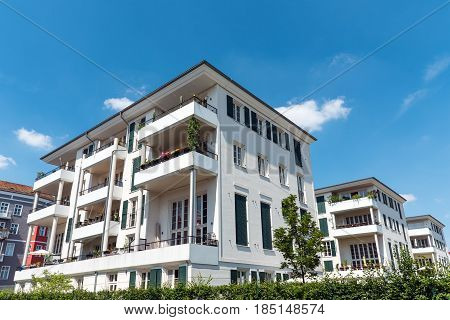 White multi-family house in front of a blue sky seen in Berlin, Germany