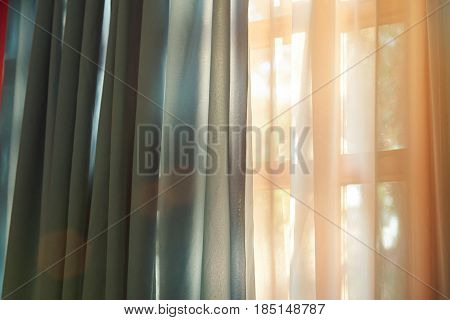 Closeup of window with curtain in sunny gold color time. Colorful window curtain