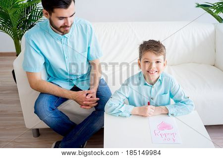 Boy offering a heart drawing to his father