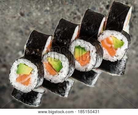 Sushi roll with salmon and avocado over cocnrete background