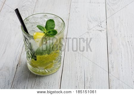 Cocktail with lime , ice and peppermint on white wooden background with copy space .