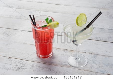 Cocktails set. Margarita, red alcohol cocktail on wooden background close up .