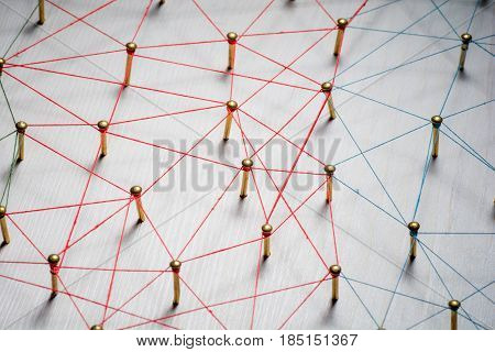 Linking entities. Network, networking, social media, internet communication abstract. A small connected to larger . Web of gold wires on rustic wood.
