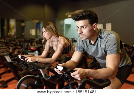 Attractive woman and man biking in the gym exercising legs doing cardio workout cycling bikes. Couple in a spinning class wearing sportswear. poster