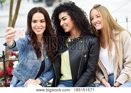 Multi-ethnic Young Women Taking A Selfie Photograph Together Outdoors