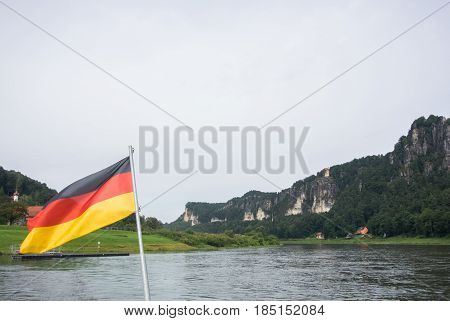 German Flag At Ferry Through The Elbe At Kurort Rathen Village And Bastei Rocks At The Background, S