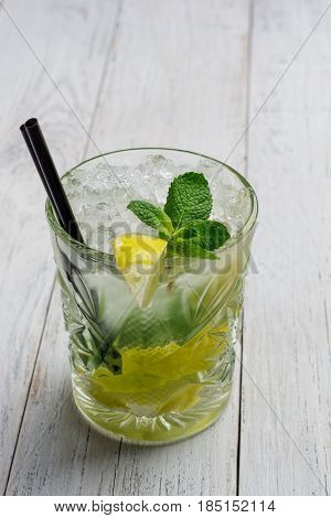 Mojito cocktail on white wooden background close up.