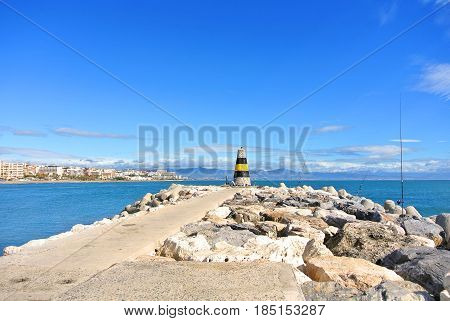 A View To Mediterranean Sea, A Lighthouse With Breakwaters, Fishing Rods Of Locals And Torremolinos