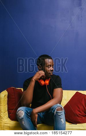 Thoughtful alone african man sit on couch at home an looking to the right side of blue background. Lazy weekend, loneliness, leisure , meloman, music concept.