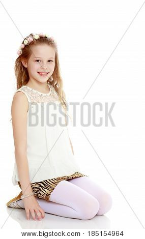 Beautiful little long-haired Caucasian girl posing in Studio.The girl knelt on the floor.Isolated on white background.
