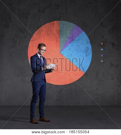 Business man with computer tablet standing on a diagram background. Business, office, career, concept.
