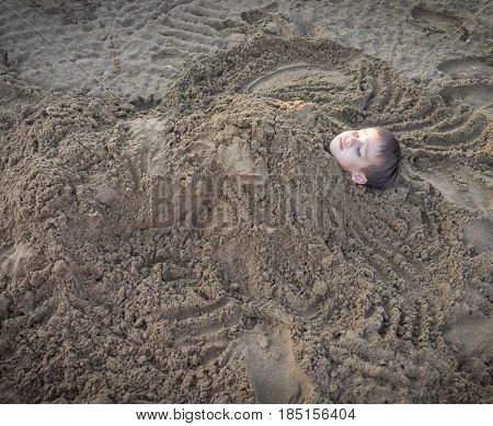 Cute kid burried in the sand for fun