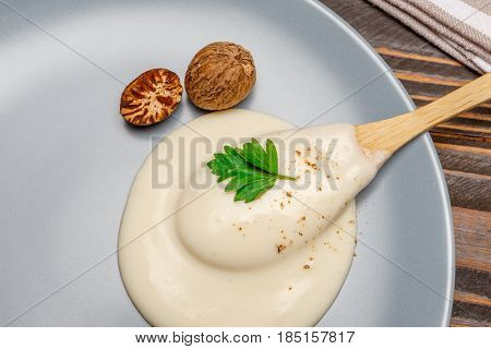 Traditional bechamel and nutmeg on the plate closeup